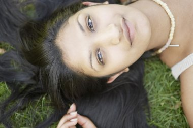Over head view of an indian girl's face laying down on grass