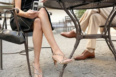 two business's legs under a coffee table while in a meeting outdoors