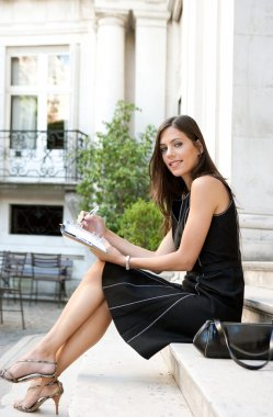 Elegant businesswoman sitting on a classic buildings steps taking notes