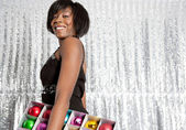 junge Balck Frau hält eine Schachtel mit verschieden farbigen Weihnachtskugeln