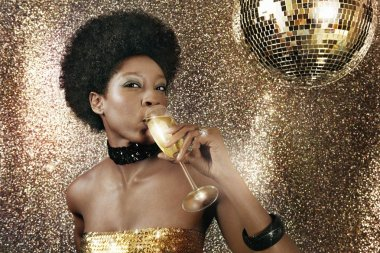 Attractive black woman in a nightclub drinking champagne