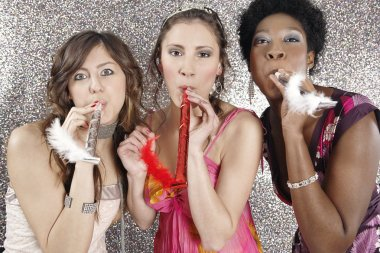 Three girlfriends blowing party blowers towards the camera