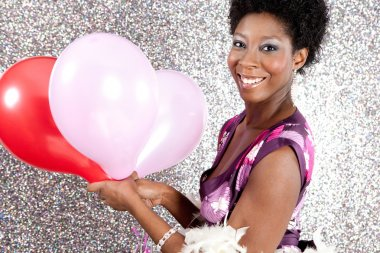 attractive young black woman holding pink and red balloons