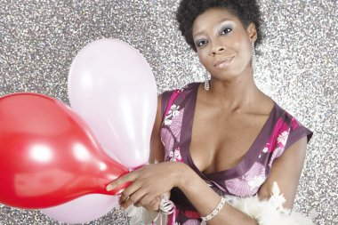 Attractive black woman holding pink and red balloons