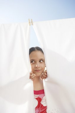 young girl peering through bed linen hung to dry in the sun on a clothes line