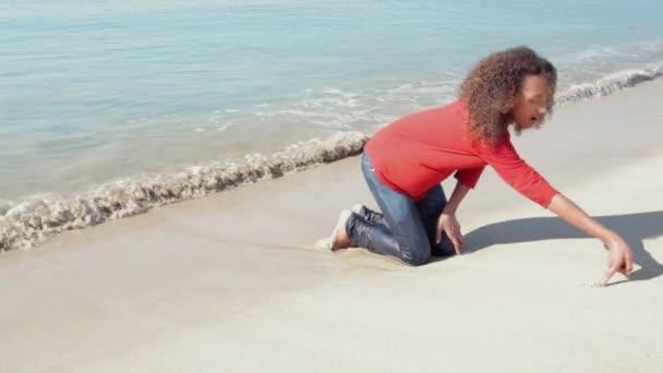 dívka nakreslit srdce na pobřeží pláži s bílým pískem