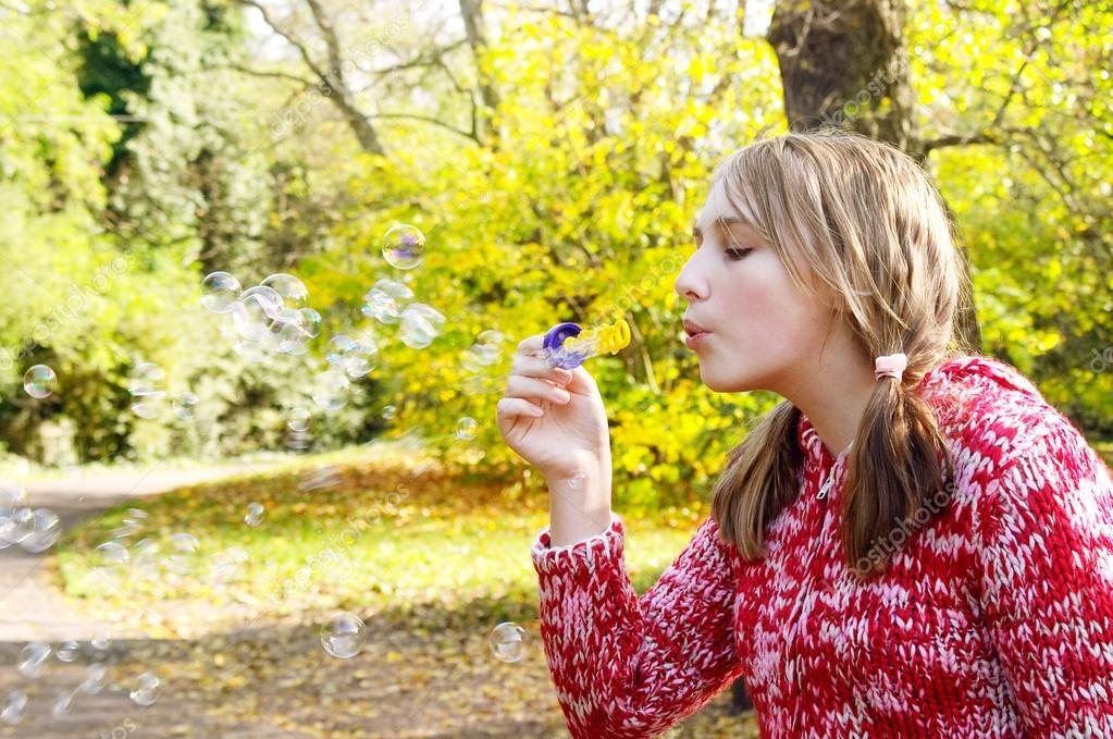 Girl in a park blowing soap bubbles