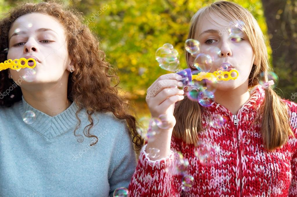Two girls blowing soap bubbles
