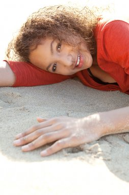 Girl laying down on a golden sand