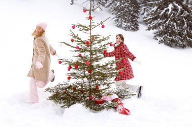 Girls running around christmas tree