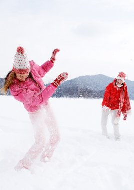 Two girls playing games and having fun in in winter