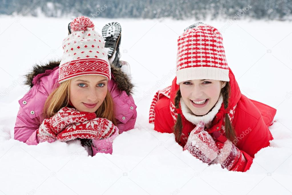 Two women laying down together on white snow