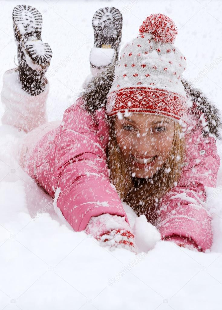 Young woman falling down in the snow