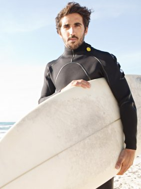 Young attractive surfer standing