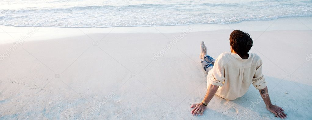 Young man sitting on beach