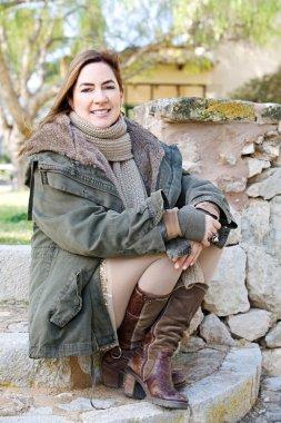 Woman sitting at  stone wall