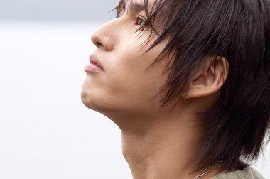Japanese young nostalgic man looking up