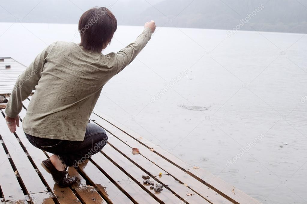 Man crouching on the pier of a lake
