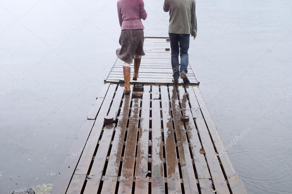 Couple walking together on a wooden pier