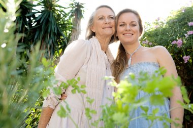 Mother and daughter standing in home garden