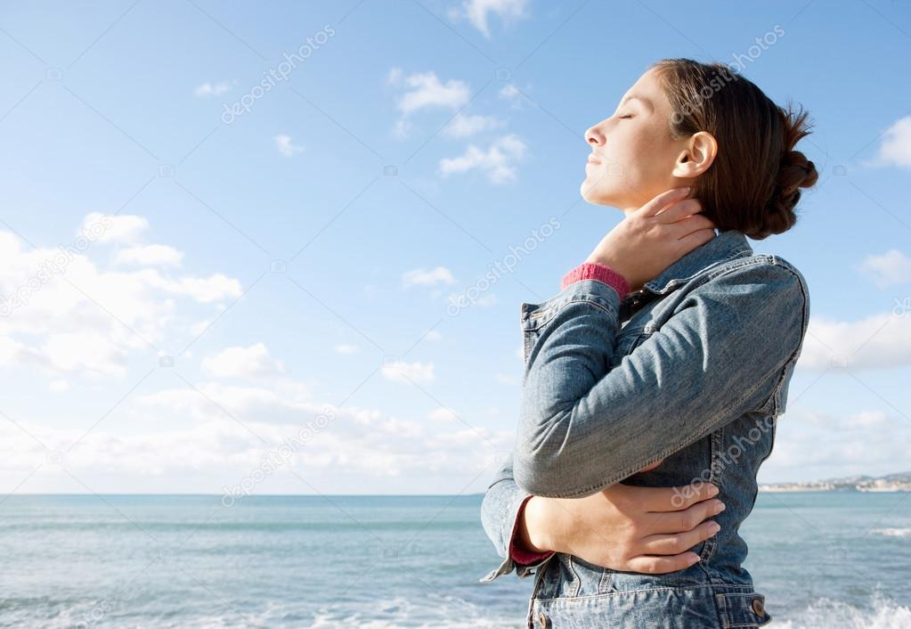Woman facing the sea and breathing fresh air
