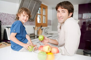 Dad with his son together in a home kitchen