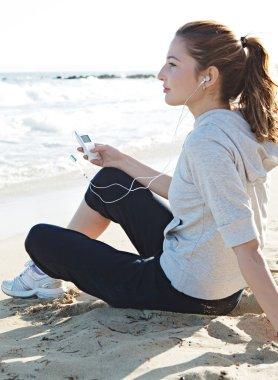 Woman sitting on a white sand beach shore