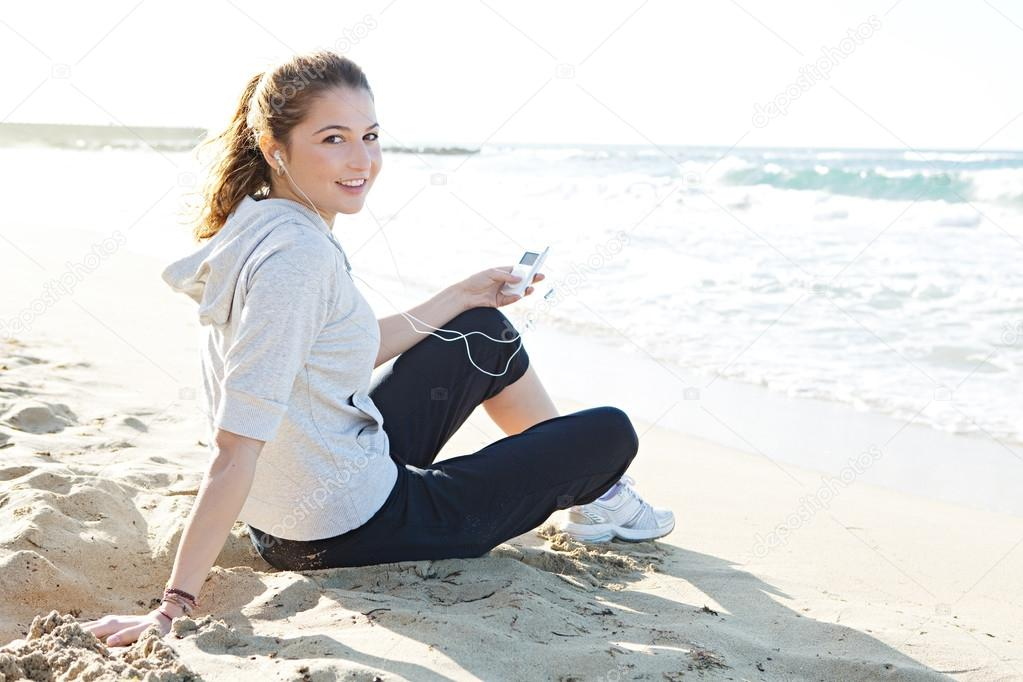 Woman sitting on a white sand beach shore