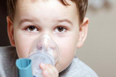 boy using inhaler for asthma.