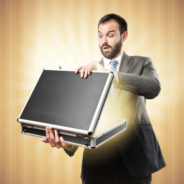 Young businessman open his briefcase over textured ocher background