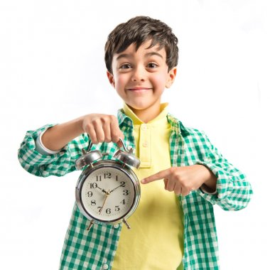 Boy holding an antique clock over white background