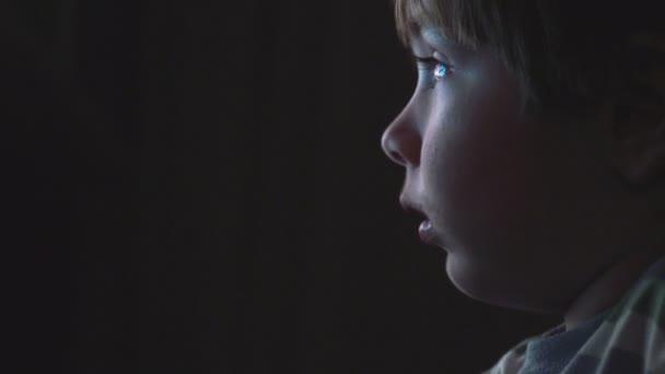 niño viendo dibujos animados en un cuarto oscuro en un equipo ...