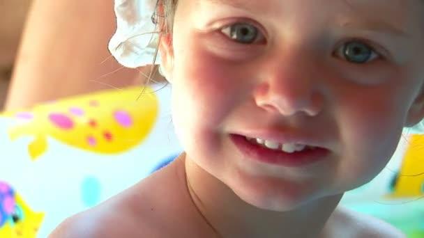 holčička hraje v bazénu. stříkající vodě a do vody