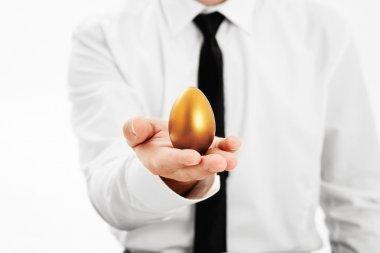 Businessman holding a golden egg