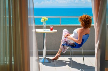Rear view of young red haired female relaxing and enjoying sea view on a hotel balcony at a sea resort, Nesebar Bulgaria, Black sea stock vector
