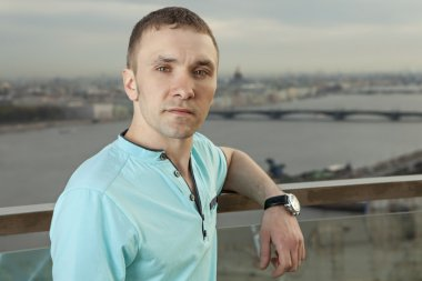A young man in a turquoise shirt, short sleeve, portrait against the background of a European city. One person, a male, short hair. One person, a male, short hair, outdoor, Caucasian, Slav, Russian,