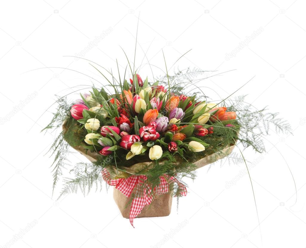 A large bouquet of color tulips in a square vase. Square floral arrangement of tulips of different colors. The isolated image on a white background.