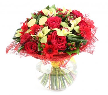 Floral composition in glass, transparent vase: red roses, orchids, red gerbera daisies. Isolated on white background. Floristic composition, design a bouquet, floral arrangement.