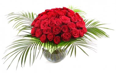 A large bouquet of red roses in a transparent glass vase. The isolated image on a white background.