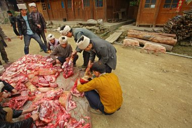 Farmers cut up and sort asian pork in chinese countryside.