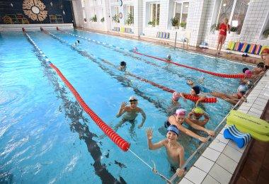 Schoolchildren swim in the covered sports public swimming pool.