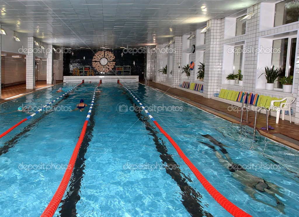 Interior public indoor swimming pool with vacationers people.