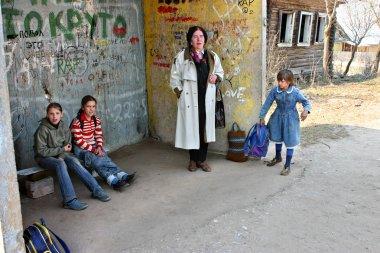 Russia, rural schoolgirls waiting transport at the bus stop