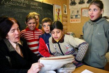 School class in the Russian village school children pupils gathered around a schoolteacher.