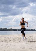 Fotografia ragazza corre lungo la spiaggia