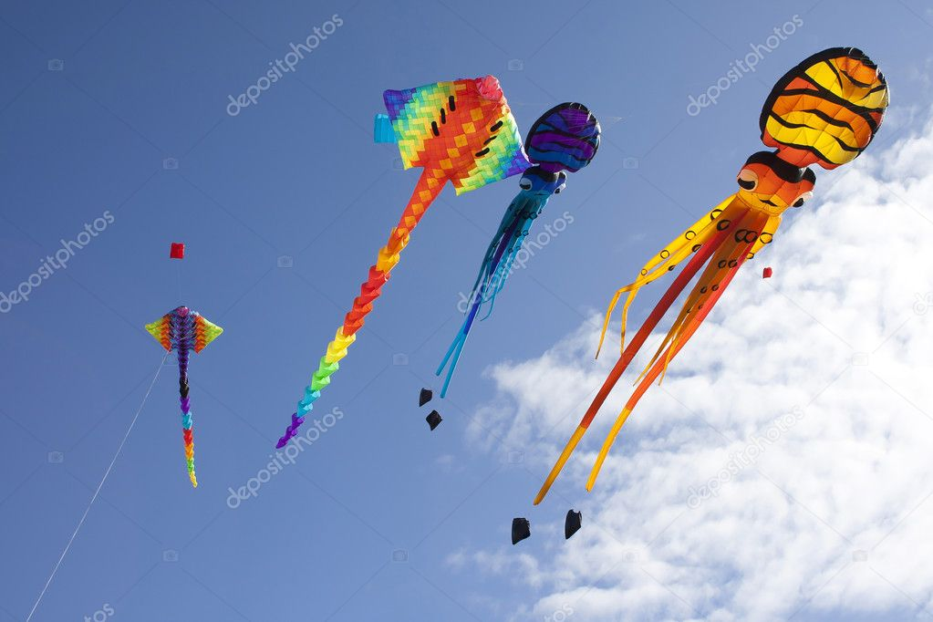 Colorful flying kites against a blue sky.