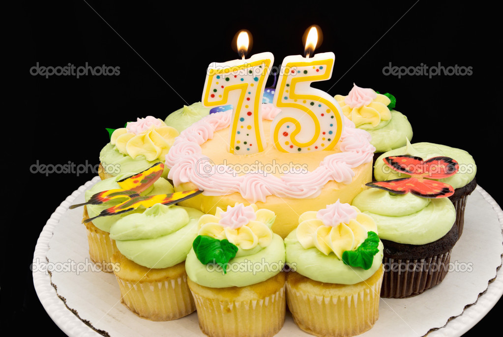 Birthday Cake With Pastel Colored Butter Cream Icing Surrounded By Yellow And Chocolate Cupcakes A 75 Candle Is Burning Photo Clayball