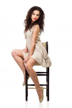 Young woman in linen dress sitting on tall chair