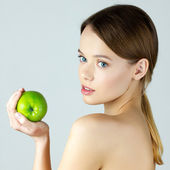 Beauty portrait of young woman holding green apple