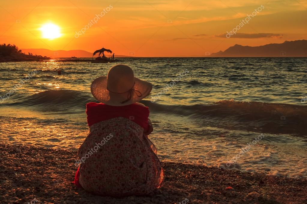 Thinking Woman sit in the sunset on the beach